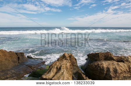 Indian Ocean seascape with foamy waves and limestone edged beach under a blue sky with clouds at Penguin Island in Rockingham, Western Australia.