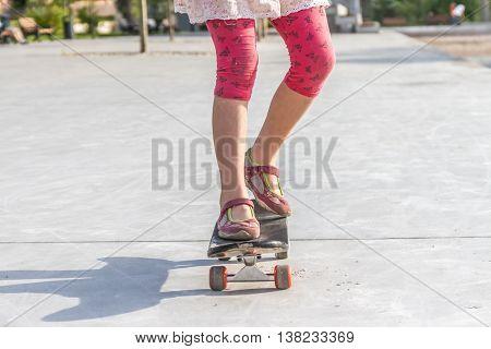 close up of girl's feet standing on modern short cruiser skateboard on asphalt background