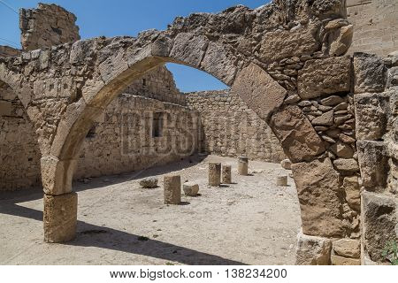 Ancient stone arch on blue sky background. Archaeological excavations in Kolossi castle. Cyprus
