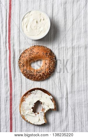 Overhead view of a sliced bagel, one half spread with cream cheese. A crock full of spread on a kitchen towel.