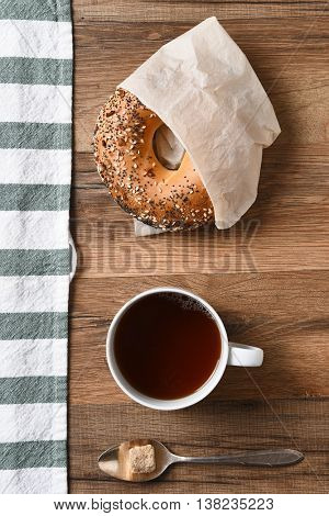 High angle view of a bagel, cup of coffee, and spoon with raw sugar lump with a striped towel.