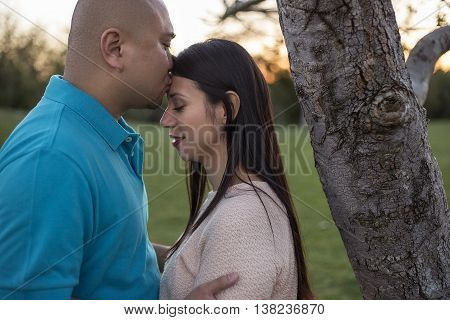 Young latino couple on a romantic date at a park during sunset