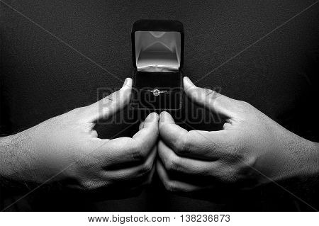 Close up of man holding an engagement ring in a heart gesture looking nervous