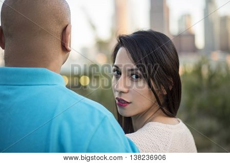 Latino couple on a date in a park looking at downtown Los Angeles cityscape