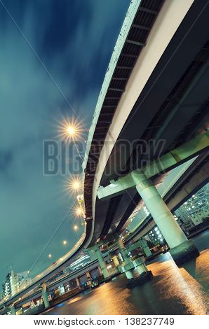 tilted huge highway structure over Sumida river in Tokyo by night