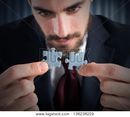Businessman joins two pieces of a puzzle