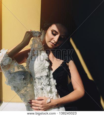 bride sitting on a windowsill and holds wedding dress