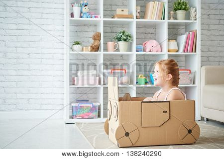 Side view of girl driving cardboard car at home