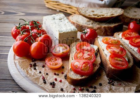 Rustic breakfast with homemade bread branch of tomatoes tofu and pepper on the round wooden desk. Country breakfast concept