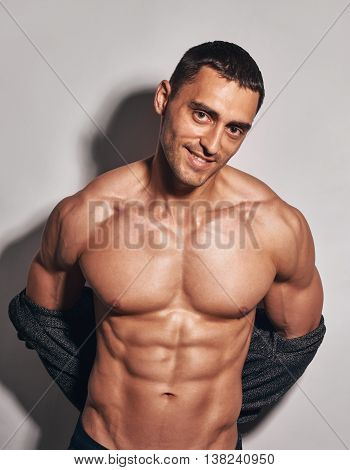 muscular man in unbuttoned shirt on grey background. shot with shadow