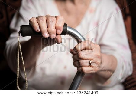 Old Woman Sitting With A Cane