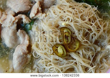 thin rice noodle with gravy sauce topping slice pickled chili