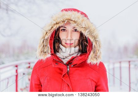 Girl in a red coat with a hood walking in the winter park