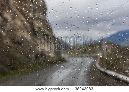 View of the bend asphalt road on a mountain pass through window glass of the car covered by rain drops
