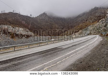 Scenic view of the bending asphalt mountain road through the pass part of the mountain serpentine in cloudy weather with fog