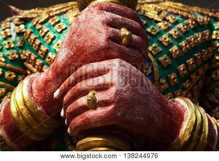 Yak guardian demon sculpture hands close-up in a Thai temple. Asian god colorful statue in a shrine
