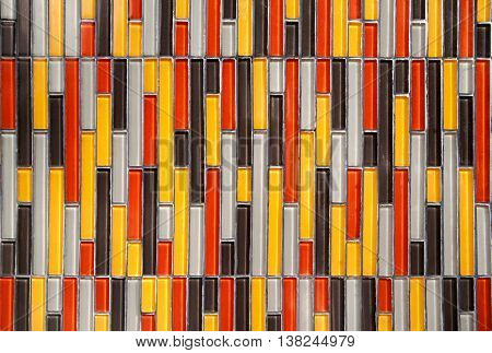 Colorful glass vertical rectangular tiled wall background: yellow red white black pattern. Multicolor tiles