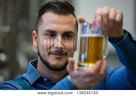 Close-up of brewer testing beer at brewery