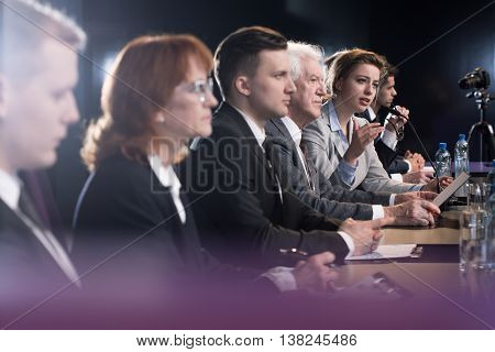 Formally dressed group of people at a conference table with one of the women speaking to microphone