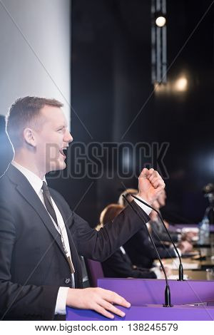 Enthusiastic young man delivering a fiery speech at a conference table