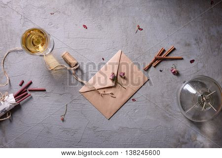 Wedding or valentine's day.Glass of wine,envelope and aroma sticks on grey background.Love letter or romantic message.Top view.