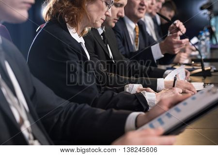 Close-up of a middle-aged woman taking notes by a conference table