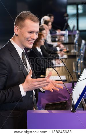Smiling man in a suit speaking enthusiastically during a conference