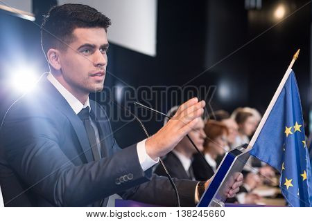 Young speaker talking to a microphone at a conference table with an EU flag