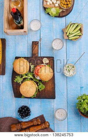 Various burgers and light beer on a blue wooden table and light beer top view