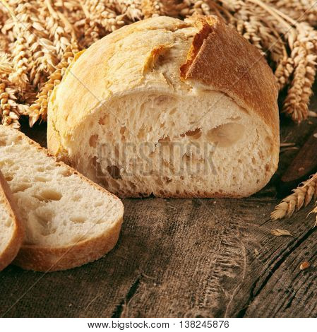 Loaf of bread with ears of wheat on natural wooden table closeup
