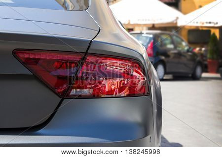 Rear light of parked grey graphite colour modern car