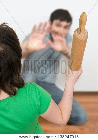 Angry Woman Is Attacking Henpecked Man With A Roller Pin. Divorc