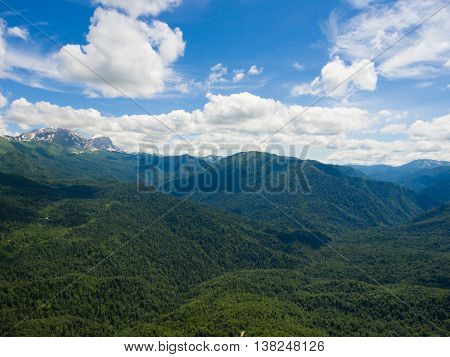 Aerial Photo. Mountain Valley. Landscape With Mountain Peaks Covered With Snow, Cloudy Sky And A Seg