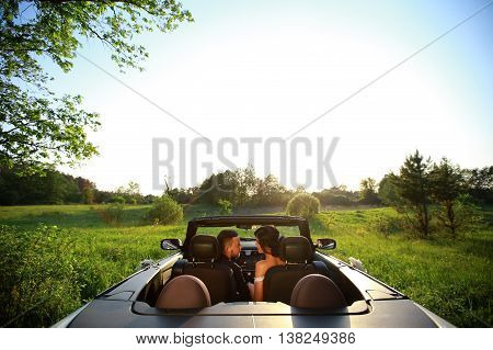 bride and groom. Young wedding couple enjoying romantic moments outside on a summer meadow. Happy bride and groom on their wedding. Stylish beautiful happy bride and groom wedding celebrations