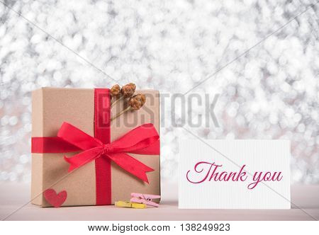 Picture of gift box with red ribbon and message thank you on greeting card blur bokeh gray background. congratulation concept