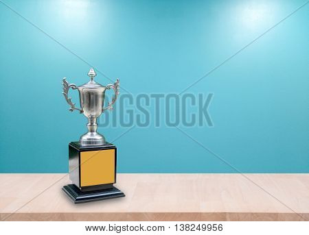 champion silver trophies on wood table with lighting victory. (business success and sport success concept)