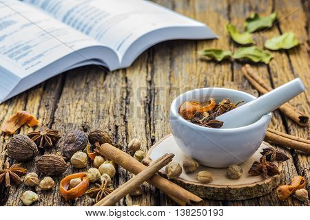 A photo of Mortar Grinder Herb and herbal with Herbal Pharmacopoeia background on wood table Selective focus Soft focus