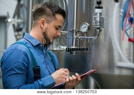 Attentive maintenance worker writing on clipboard at brewery