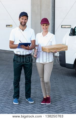 Delivery people are posing and holding goods in front of a warehouse