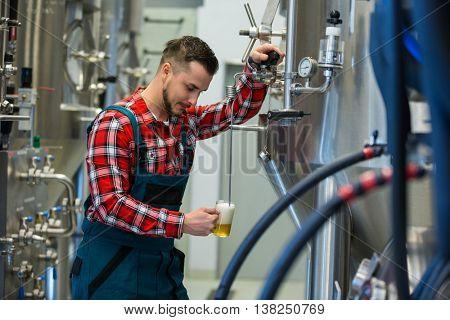 Brewer testing beer at brewery