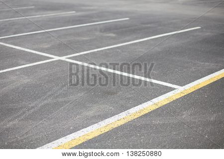Empty asphalt parking lot with white and yellow lines