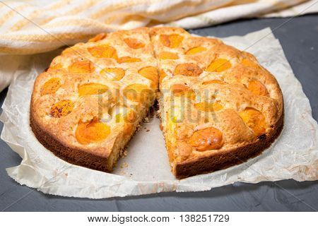 apricot pie on the baking paper with ripe apricots.