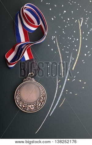 bronze medal with ribbon on the blackboard  with firework drawing