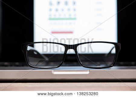 Eye chart on computer. Focus on glasses