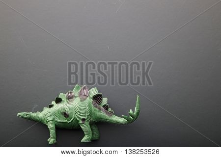 Dinosaur toy over a blackboard