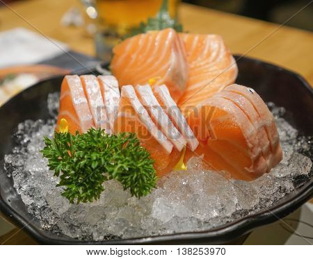 Japanese style salmon sashimi serve on bowl and crushed ice selective focus