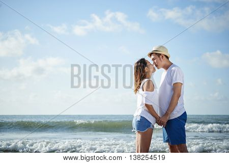 Young Vietnamese couple kissing on the beach