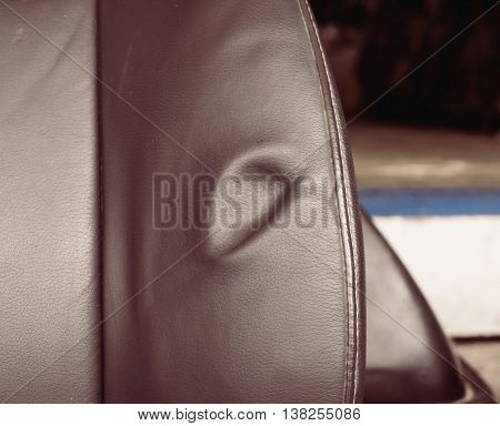 A dent pressure mark indentation on old leather vehicle car seat with selective focus and vintage effect