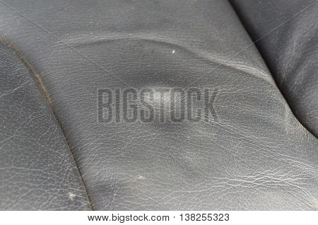 A dent pressure mark indentation on old leather vehicle car seat with selective focus