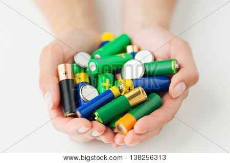 recycling, energy, power, environment and ecology concept - close up of hands holding alkaline batteries heap